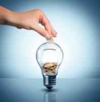 fin du tarif réglementé d'EDF. ampoule tirelire et main qui insère un euro