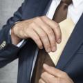 homme d'affaire glissant une enveloppe dans son veston - rétrocommissions